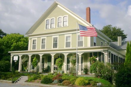 Front of the Captain Freeman Inn with a flag in the front