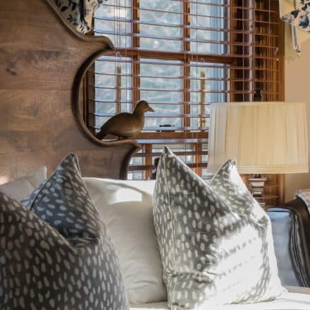 Designer grey polkadot pillows with a hand carved headboard in our Harwich room including a wooden bird on the side