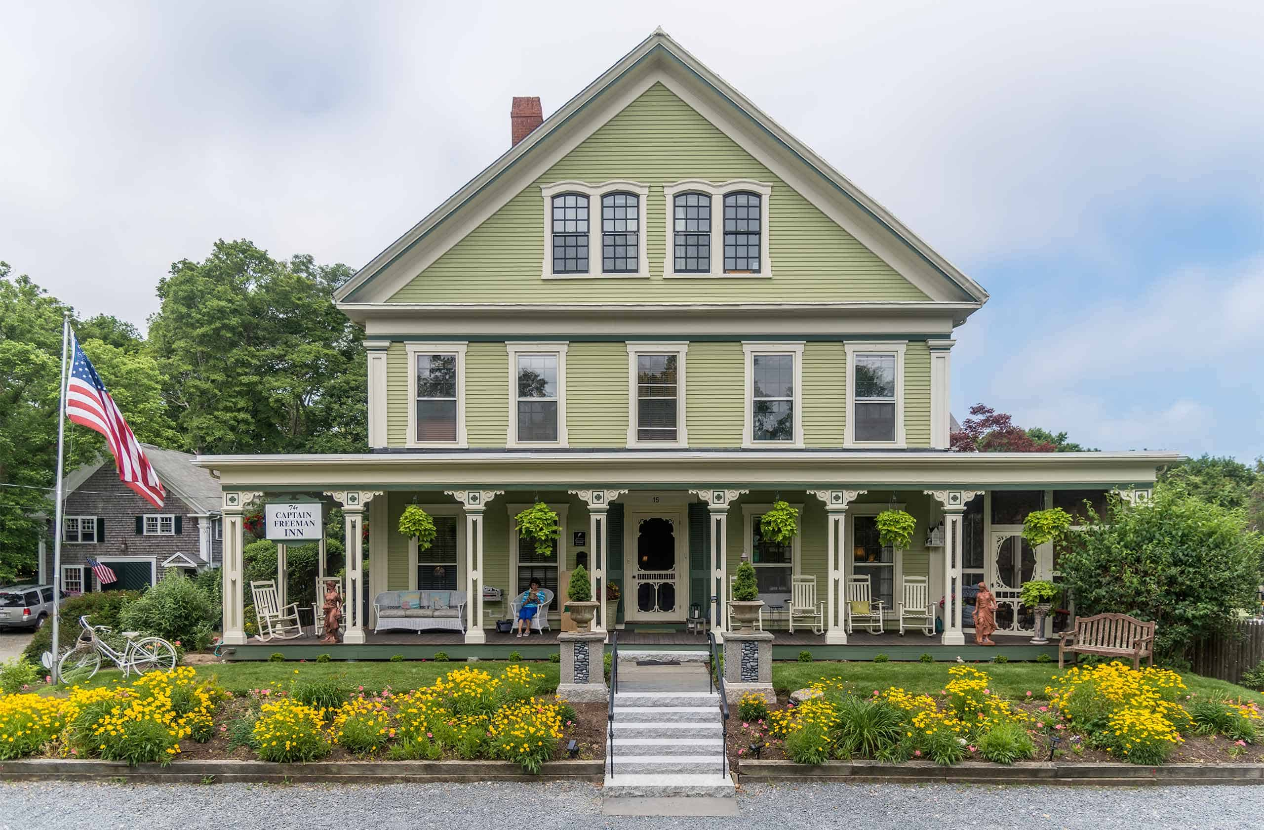 The Captain Freeman Inn from the front showing the patio deck on ground floor, 5 windows on second floor, and two large windows on the third floor. Gardens are in bloom with an American flag waving.