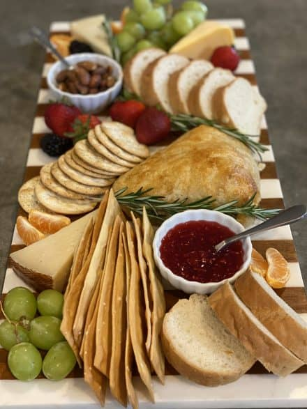 Cheese Board with several cheeses, bread, fresh fruit, jam